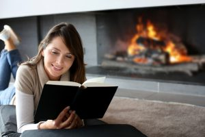 woman reading infront of fireplace